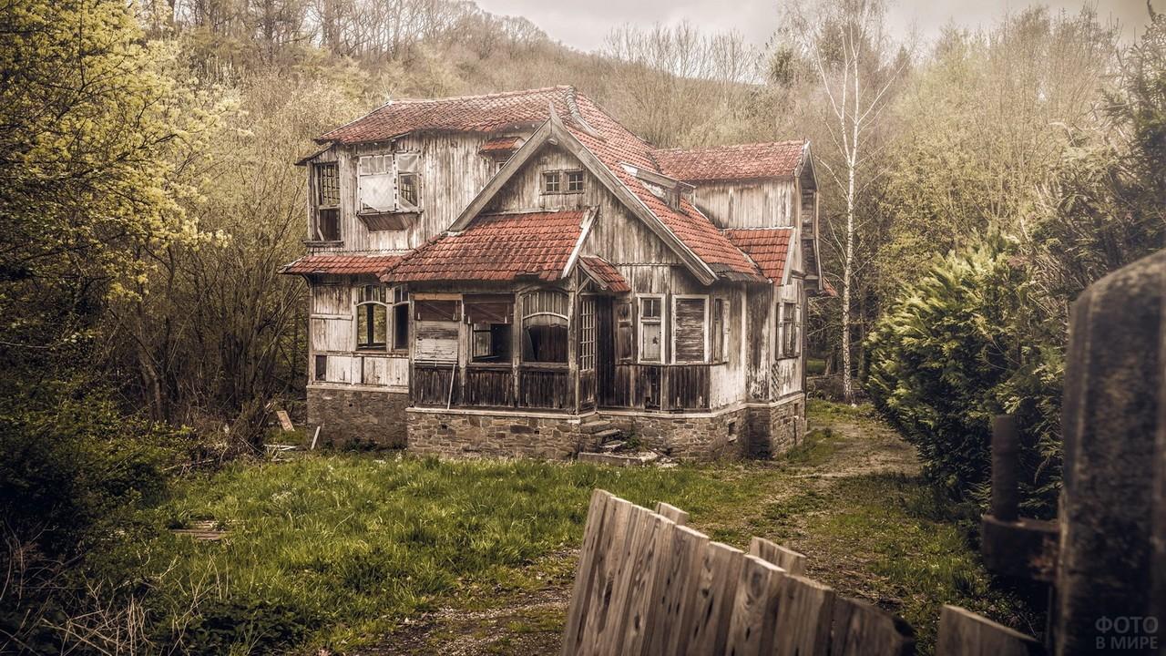 Двухэтажный дом с красной крышей в глуши