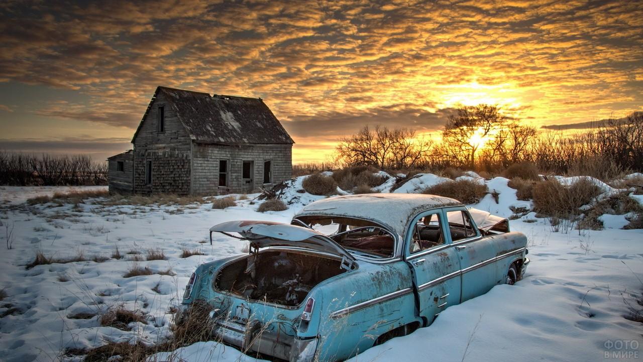 Старый автомобиль рядом с домом на закате