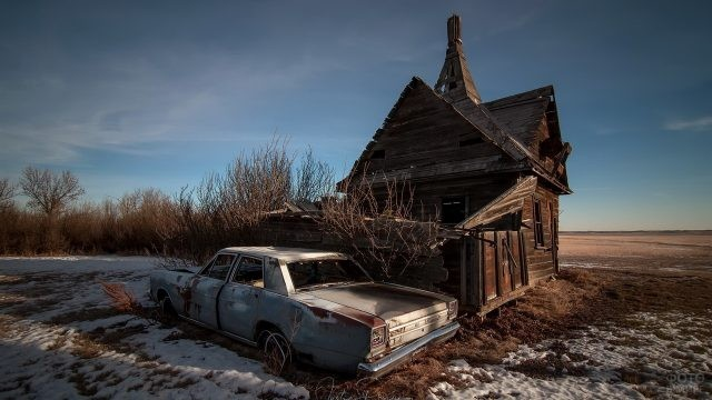 Заброшенный автомобиль возле старого дома