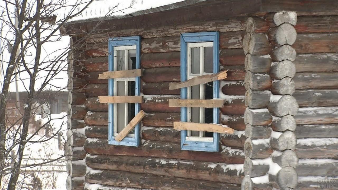 Заколоченные окна бревенчатого дома