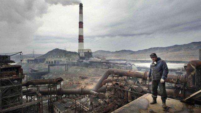 Рабочий на фоне разрушенных труб старого завода