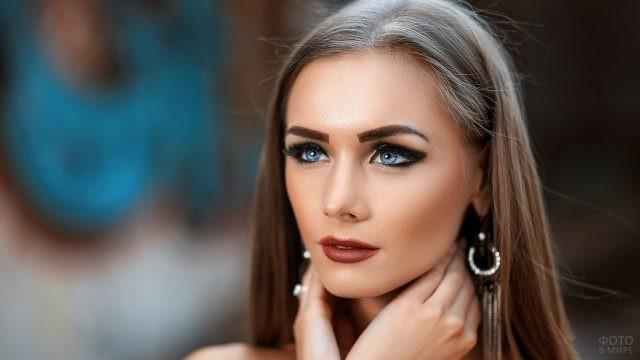 Голубоглазая девушка с нарисованными бровями и чрезмерным макияжем