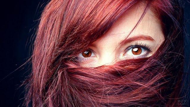 Рыжая девушка с оранжевыми глазами закрыла лицо волосами