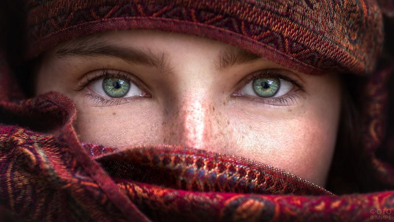Зеленоглазая рыжая девушка закрывает лицо шарфом