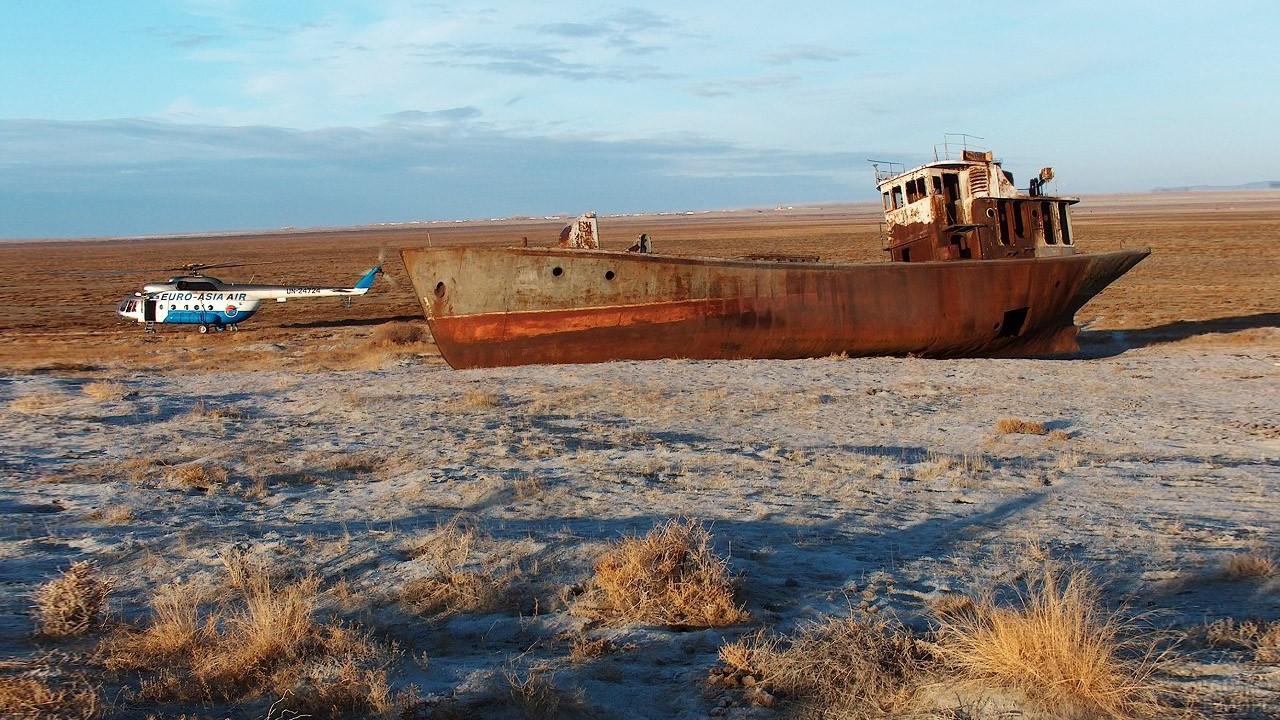 Вертолёт у одного из брошенных рыбацких кораблей в Аральском море