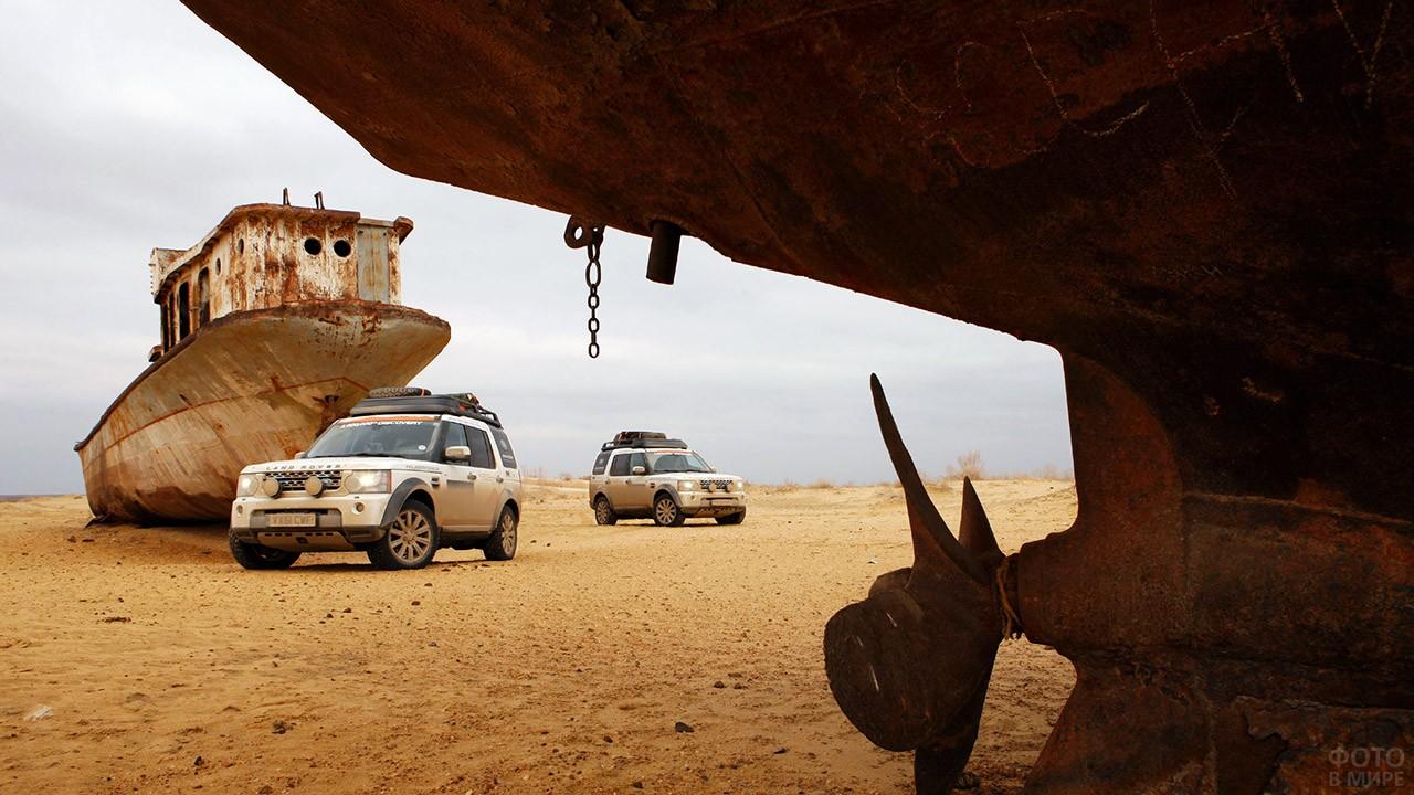 Внедорожники лэнд-ровер среди кораблей на месте Аральского моря