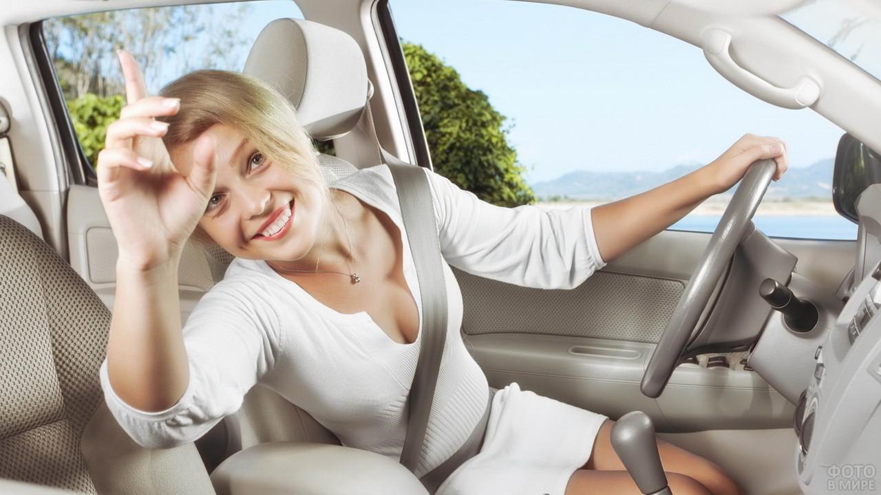 Блондинка в белом платье машет из автомобиля