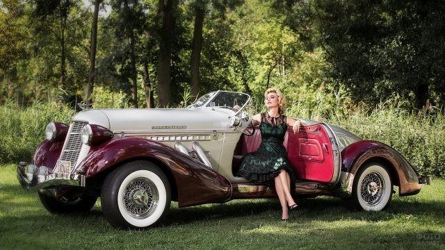 Блондинка в чёрном платье за рулём ретро-автомобиля
