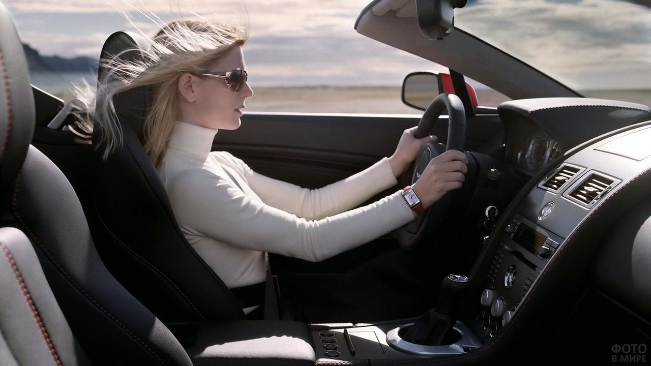 Блондинка за рулём автомобиля в солнцезащитных очках в профиль