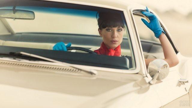 Брюнетка в синих перчатках за рулём автомобиля