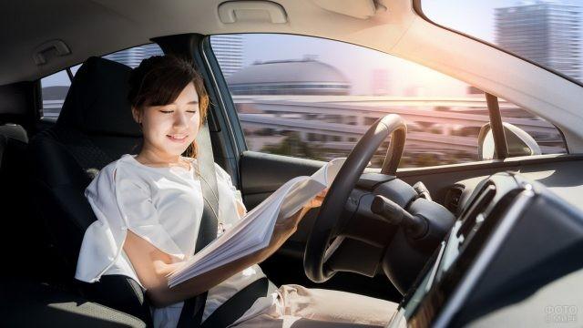 Девушка азиатской внешности читает журнал за рулём автомобиля