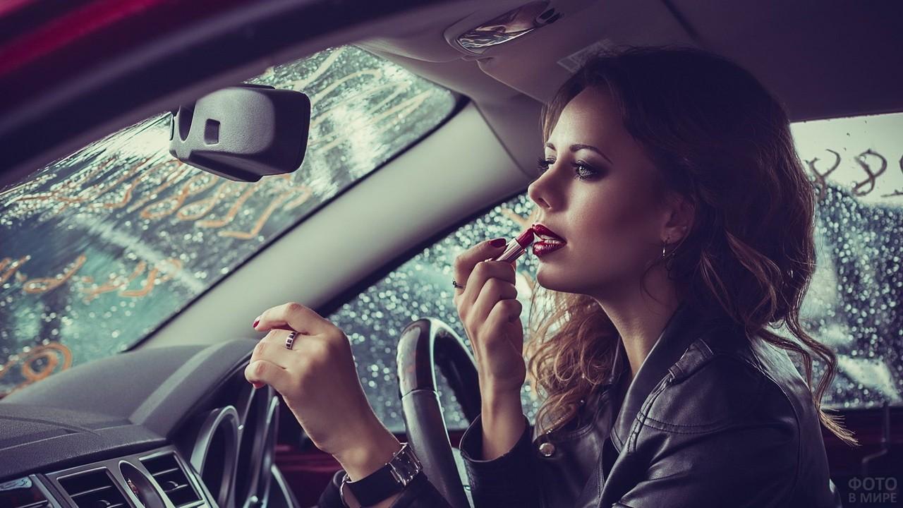 Девушка красит губы за рулём автомобиля