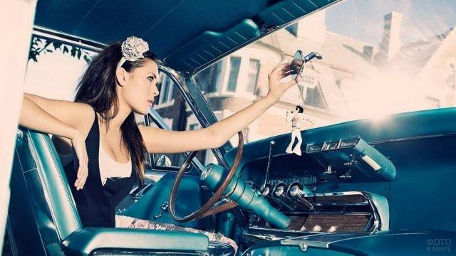 Девушка поправляет зеркало заднего вида в автомобиле