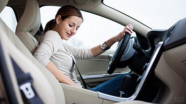 Девушка пристёгивается за рулём автомобиля
