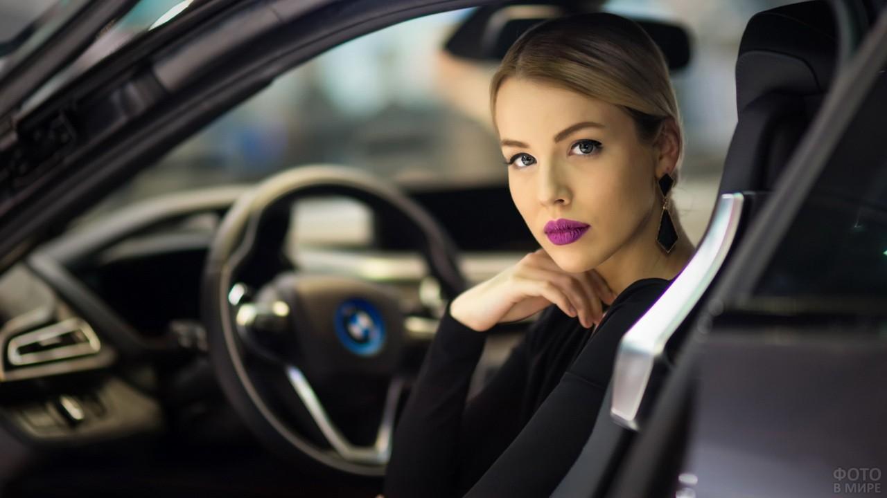 Девушка с лиловыми губами за рулём автомобиля