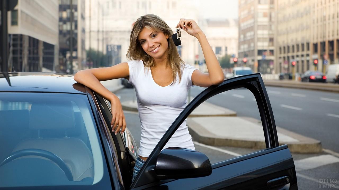 Девушка в белой футболке стоит возле автомобиля с ключами в руке
