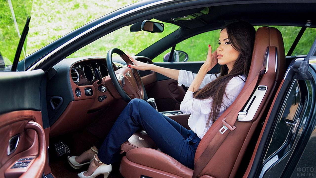 Девушка в белых туфлях за рулём автомобиля