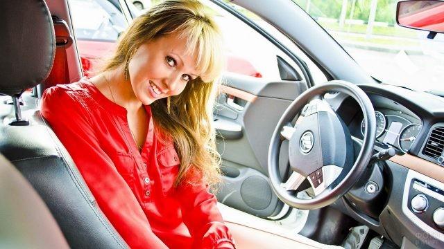 Девушка в ярко-красной блузке улыбается за рулём автомобиля