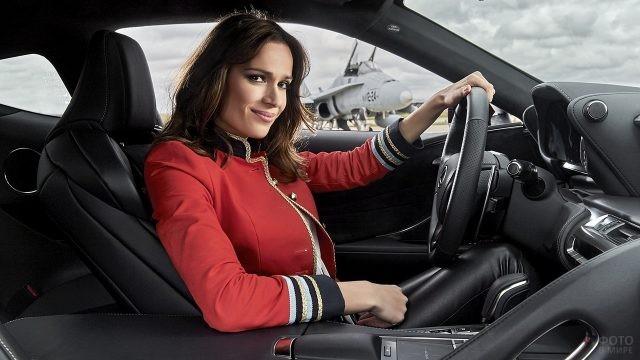 Девушка в красной куртке за рулём автомобиля