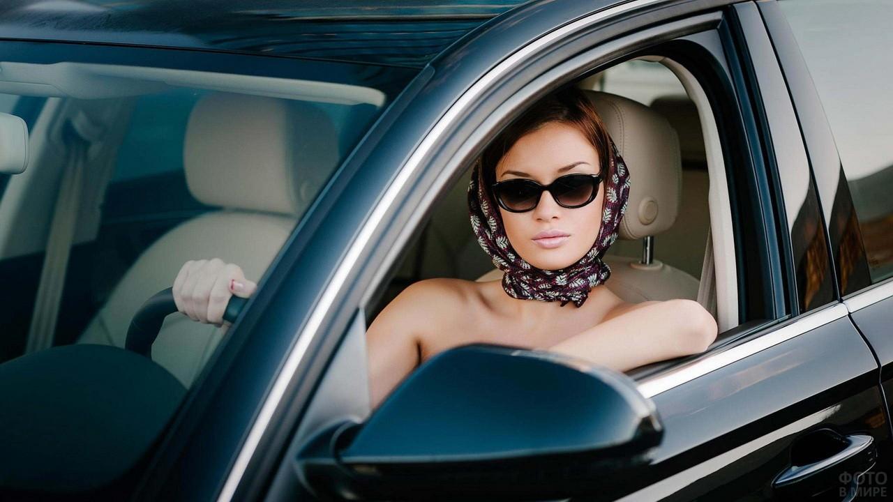 Девушка в платке и солнезащитных очках за рулём автомобиля