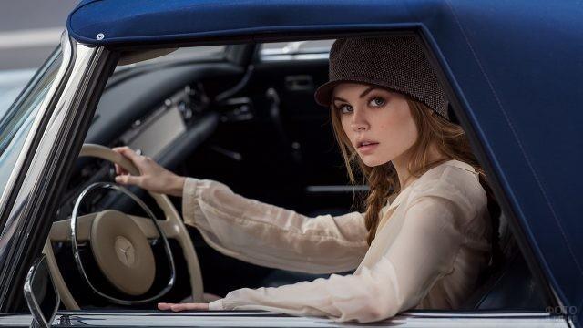 Девушка в шапке-гаврош за рулём автомобиля
