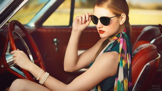 Девушка в солнцезащитных очках с браслетом на руке за рулём авто
