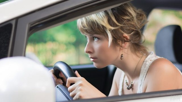 Девушка за рулём автомобиля на светофоре