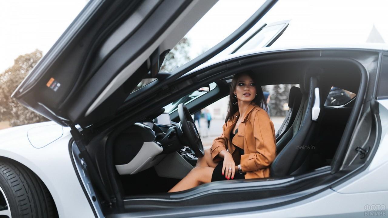 Девушка за рулём автомобиля с поднятыми вверх дверями