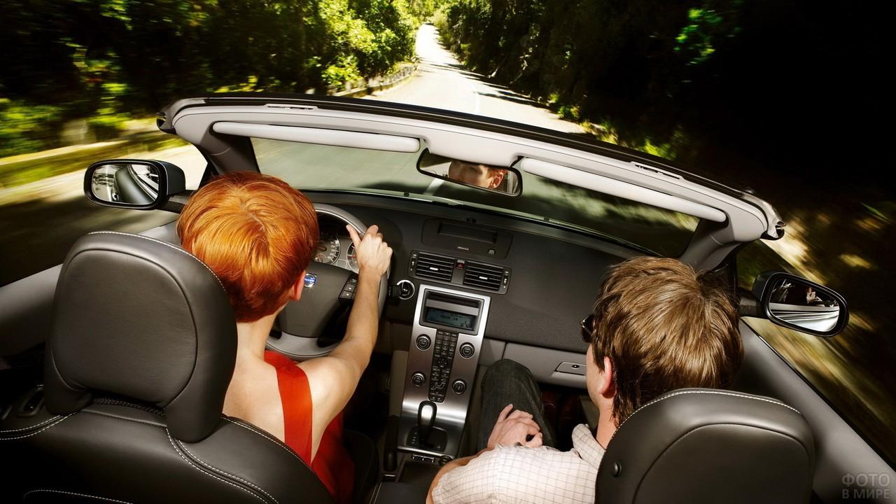 Парень и девушка с рыжими волосами за рулём кабриолета