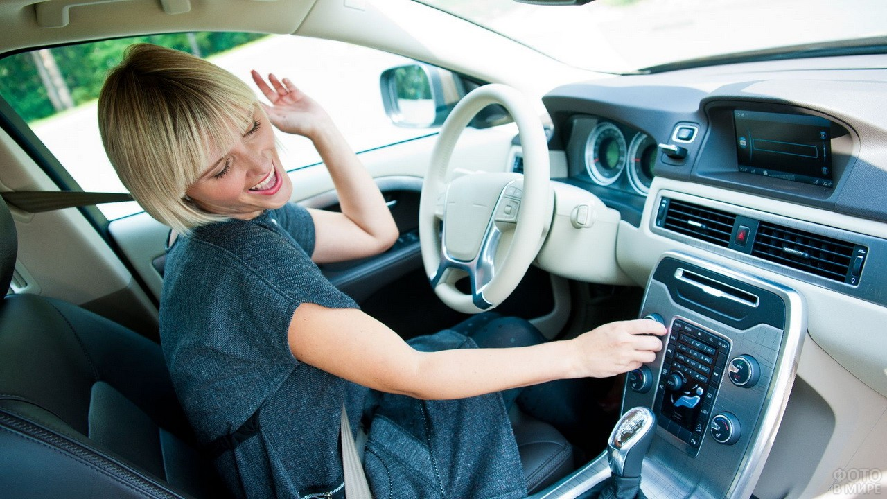 Весёлая блондинка за рулём автомобиля слушает музыку