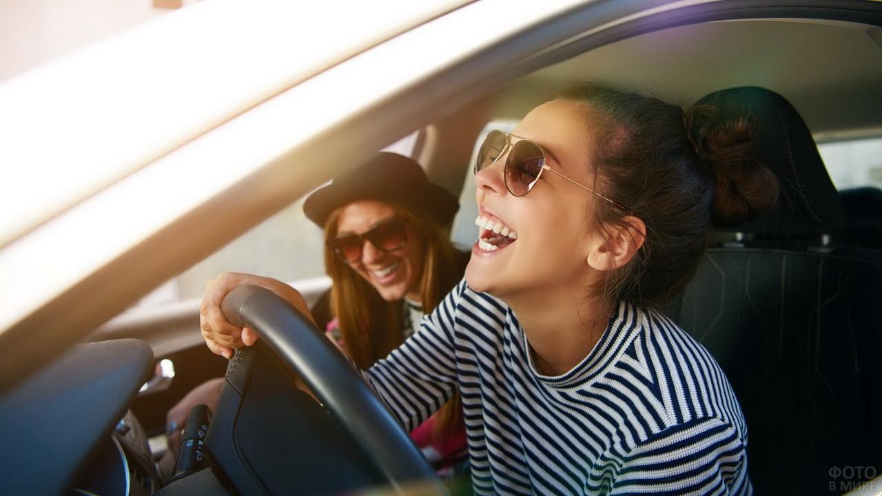 Весёлые девчонки в солнцезащитных очках за рулём автомобиля