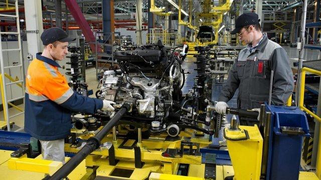 Рабочие на сборке двигателя в цеху автомобильного завода