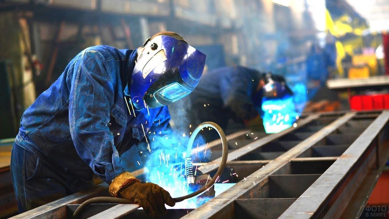 Рабочий работает болгаркой на заводе в цеху