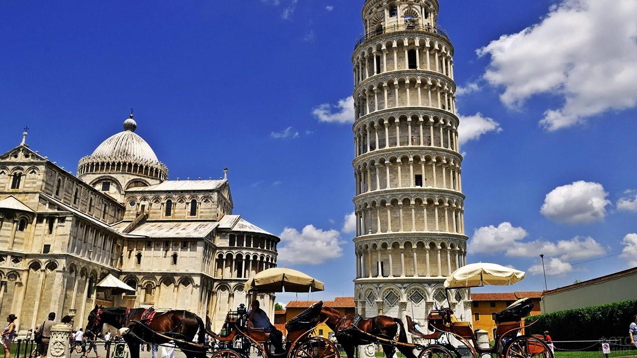 Конные повозки для туристов у подножья Пизанской башни