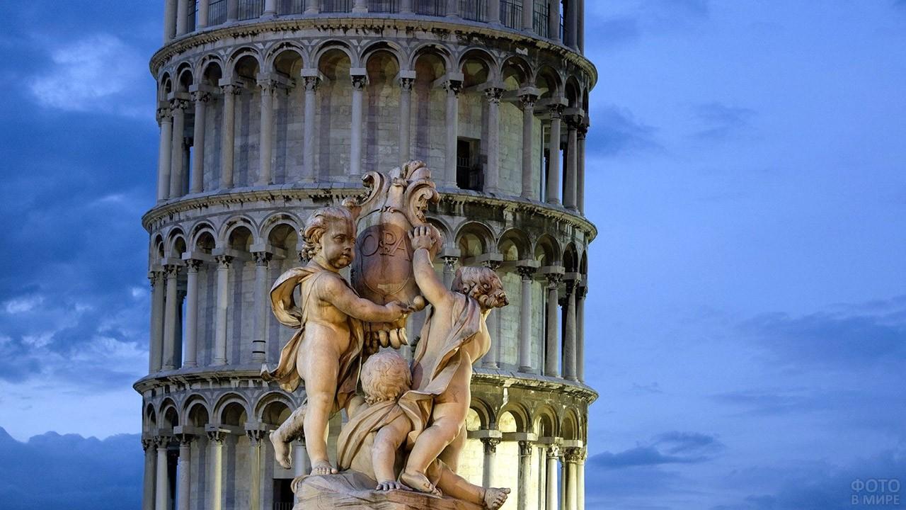 Скульптурная композиция на фоне Пизанской башни в вечерней иллюминации