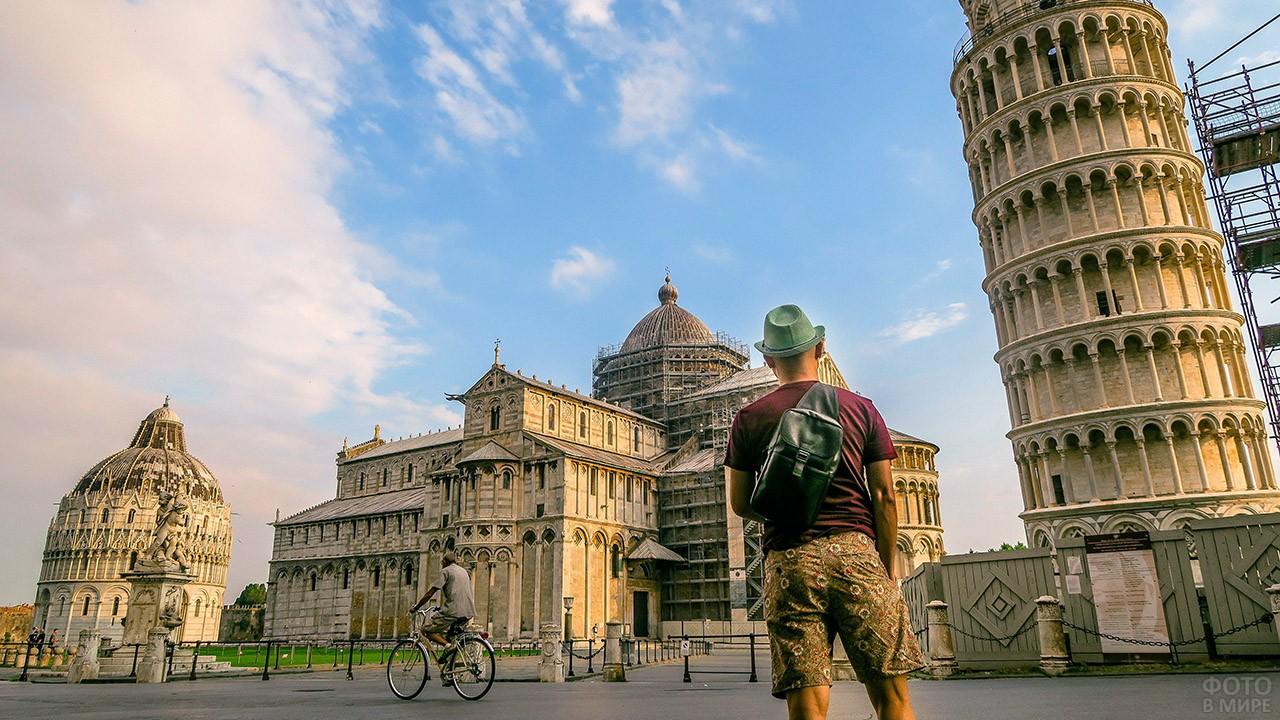 Турист любуется Пизанской башней и собором