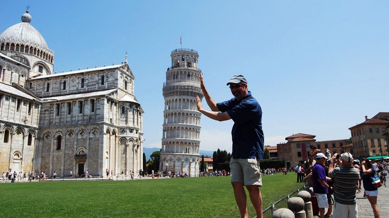 Турист традиционно поддерживает Пизанскую башню на фото
