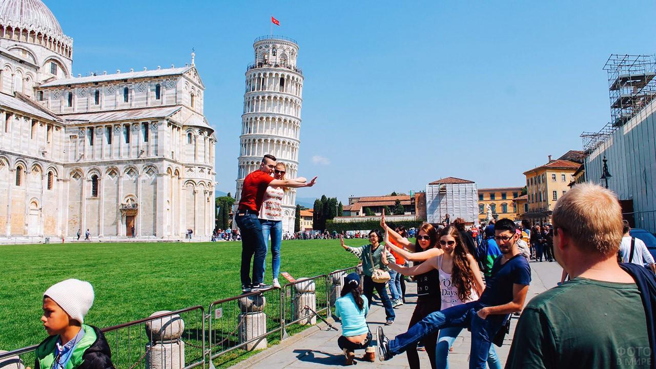 Туристы фотографируются на фоне Пизанской башни