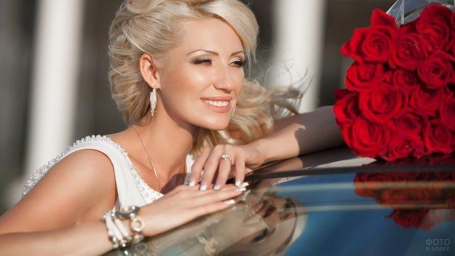 Блондинка у машины с букетом красных роз
