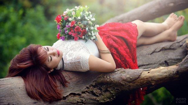 Девушка лежит на бревне с букетом