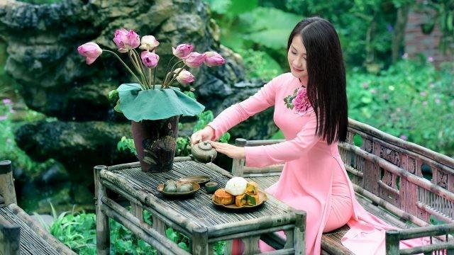 Девушка наливает чай рядом с букетом цветов в вазе