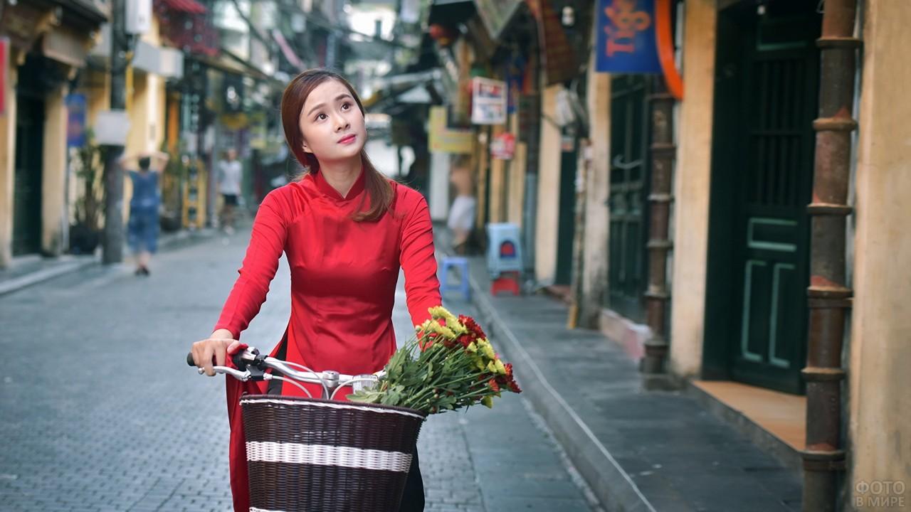 Девушка с букетом едет на велосипеде по городу
