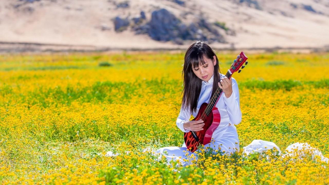 Девушка с гитарой в поле жёлтых одуванчиков