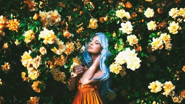 Девушка с голубыми волосами на фоне жёлтых цветов