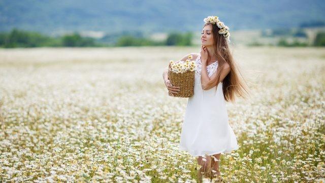 Девушка с корзиной в поле ромашек