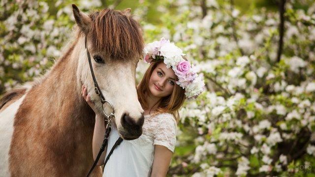 Девушка с лошадью на фоне цветущих деревьев