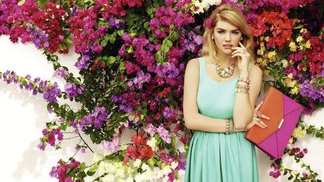 Девушка с сумочкой на фоне цветов
