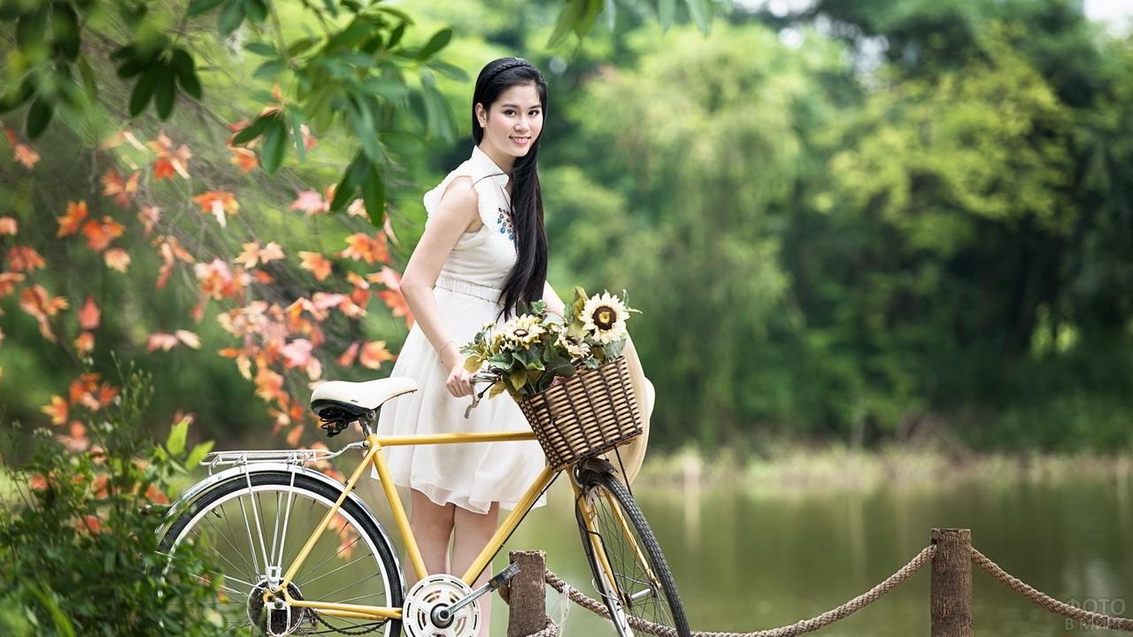 Девушка с велосипедом и цветами у пруда