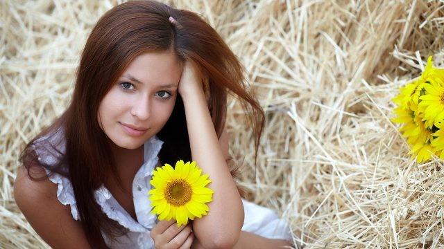 Девушка с жёлтым подсолнухом на фоне соломы