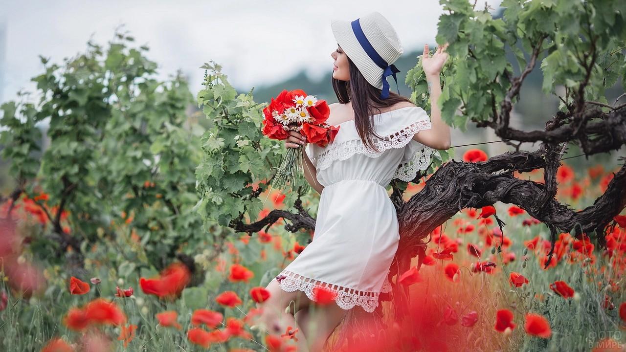 Девушка в белом у дерева с букетом маков и ромашек